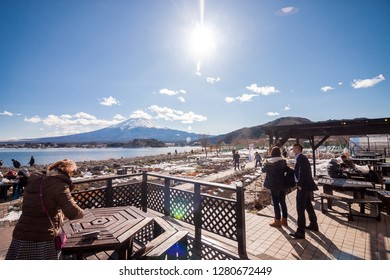 Kawaguchiko January 20, 2017 : Kawaguchiko Lake near mount Fuji with village and surrounded with white color on mountains in winter season. Blue sky in Kawaguchiko village.
