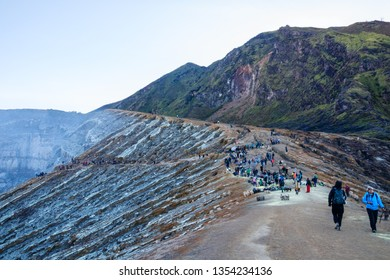 KAWAH IJEN, JAVA, INDONESIA - OCTOBER 15, 2016: View of the Kawah Ijen volcanic crater with a crowd of tourists and sulfur miners at the edge. The Ijen is a sulfur mine and a major tourist attraction.
