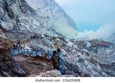 KAWAH IJEN, JAVA, INDONESIA - OCTOBER 16, 2016: View of the Kawah Ijen crater with tourists and sulfur miners climbing up the slope and toxic sulfuric gases emeging from the lake.