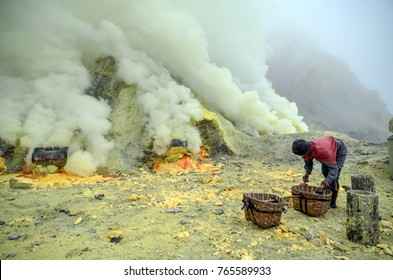 Kawah Ijen Sulfur miner in the middle of toxic sulfur dioxide gas. Each bamboo bag can carry approximately 40 kg of sulfur.