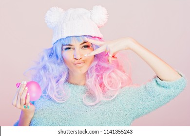 Kawaii fashion young woman with pink and purple hair, posing, swearing pastel colors. Studio lighting, medium retouch.