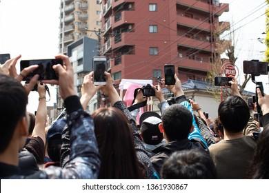 Kawasaki, Japan - April 7, 2019: The Shinto Kanamara Matsuri (Festival of the Steel Phallus) in Kanayama Shrine, Tourists taking pictures of big statue of Phallus