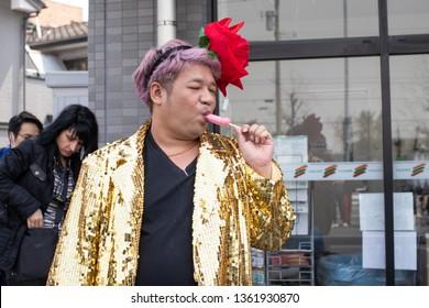 Kawasaki, Japan - April 7, 2019: The Shinto Kanamara Matsuri (Festival of the Steel Phallus) in Kanayama Shrine, Man in fancy costume eating candy lollipop in shape of phallus