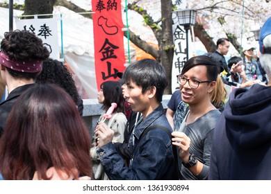 Kawasaki, Japan - April 7, 2019: The Shinto Kanamara Matsuri (Festival of the Steel Phallus) in Kanayama Shrine, Man eating candy lollipop in shape of phallus