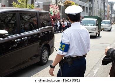 Kawasaki, Japan - April 7, 2019: The Shinto Kanamara Matsuri (Festival of the Steel Phallus) in Kanayama Shrine, policeman speeds up the crowd to let cars go