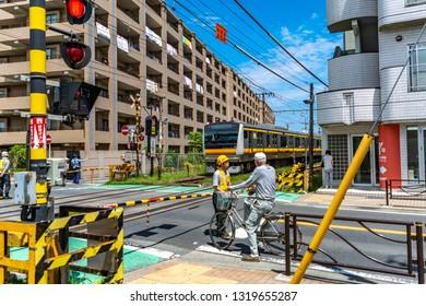 Kawasaki, Kanagawa, Japan - June 17 2016 - A railway staff ensures the safety of pedestrians during a train break down at the railway crossing near Noborito station.