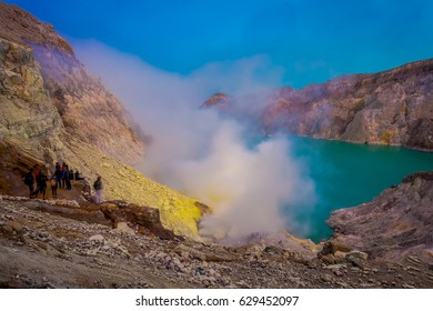 KAWEH IJEN, INDONESIA - 3 MARCH, 2017: Tourist hikers with backpacks and facial masks seen overlooking sulfur mine and volcanic crater lake