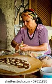 KAYA KOY, TURKEY - AUGUST 22: Unidentified woman makes traditional Turkish pancakes on August 22, 2010 in Kaya Koy, Turkey.  Kaya Koy is a popular destination for tourists to Turkey.
