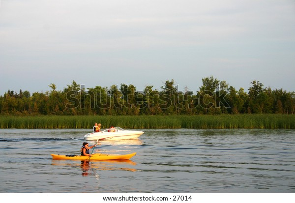 Kayak and boat on river at sunset