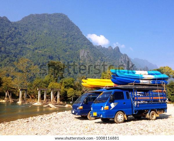 kayak boats on roof of car beside Nam Song river at Vang Vieng, Laos