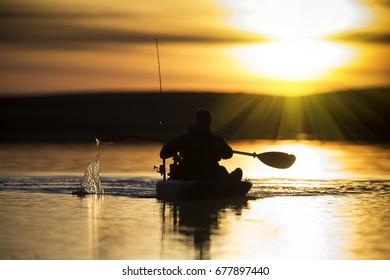 Kayak fisherman paddling into the sunset