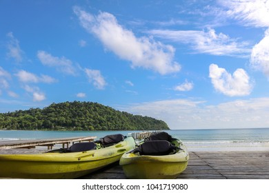 Kayak on sunny tropical beach with wooden bridge and island on Thailand