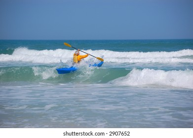 A kayak paddles through the Surf in Ponce Inlet, Florida