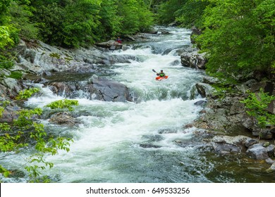 A kayak rider enjoys the thrills of the whitewater at The Sinks in Smoky Mountains National Park Tennessee