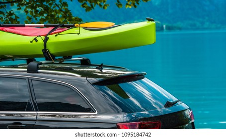 Kayak Roof Rack and the Green Kayak Mounted on the Vehicle Roof. Vacation on the Water Theme. Scenic Lake in the Background.