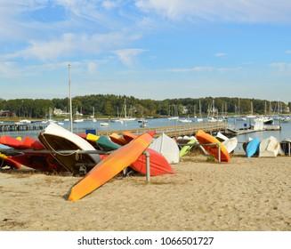 Kayak and Row Boats on sandy beach Huntington Harbor Long Island New York USA blue sky clouds