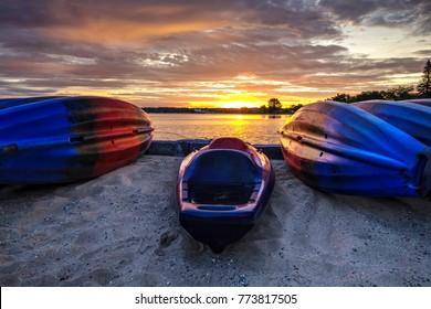 Kayak Sunrise Lake Scene. Kayaks line a sandy Lake Michigan beach at sunrise in Traverse City, Michigan.