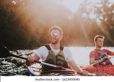 Kayak travel. Two modern stylish friends are swimming on kayaks and have fun.