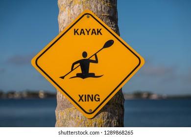 Kayak Xing - (Kayak Crossing) - yellow sign on a tree