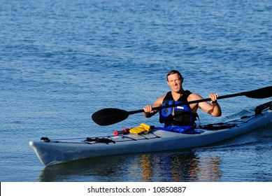 Kayaker arrives from exercises in calm blue waters of Mission Bay, San Diego, California