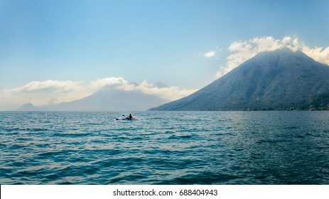 A Kayaker in the blue waters of Lake Atitlan in Guatemala, on a misty morning in front of volcano San Pedro. Further away in the mist we can see Volcanoes Toliman and Atitlan.