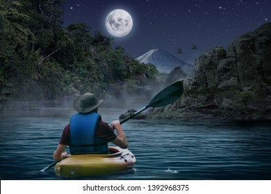 Kayaker explores a river in the rain forest by moonlight