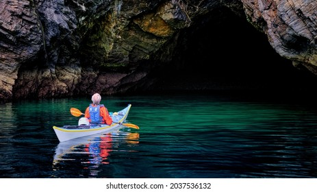 Kayaker exploring sea caves at Lybster in the Highlands