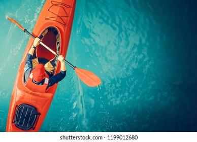 Kayaker Lake Tour Aerial Photo. Red Kayak and Caucasian Paddling Sportsman in His 30s.