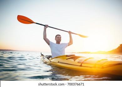Kayaker man holding oars high. Man in canoe holding oars high. Success, achievement, winning concept