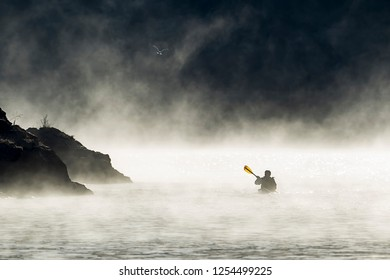 A kayaker paddles though the mist and fog in early December on Coeur d'Alene Lake by Higgens Point in North Idaho.