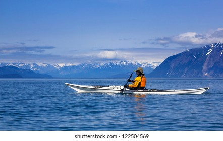 Kayaker paddling in Glacier Bay National Park with mountains on the background