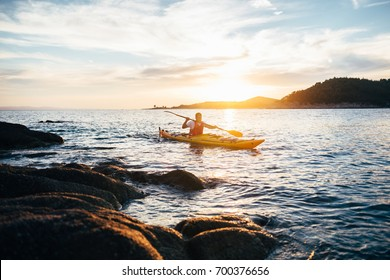 Kayaker paddling the kayak at sunset sea. Kayaking, canoe, paddling