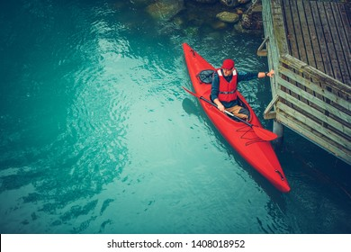 Kayaker Preparing For Scenic Tour Along Glacial Lake in the Norway. Water Sports and Recreation Theme.