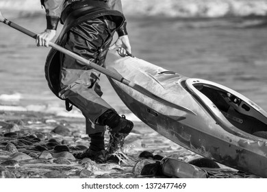 Kayaker pulling his boat along a shore