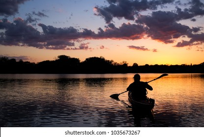 Kayaker at sunset on Lake of the Isles in Minneapolis, MN