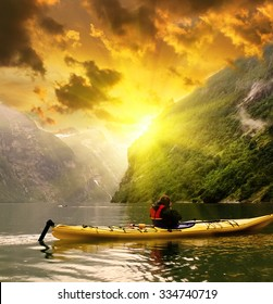 Kayaker takes a photo of dolphins at Geiranger fjord bay at sunset at Norway. Extreme travel background