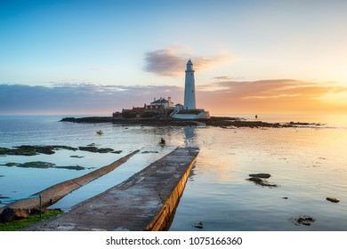 Kayakers paddle round the lighthouse at sunrise on St Mary's Island at Whitley Bay in Tyne and Wear on the Northumbria coast