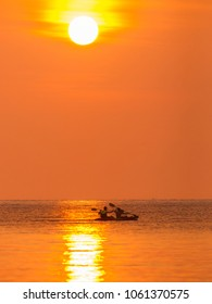 Kayakers paddle under a setting sun on a golden ocean on Ko Kut island, Thailand. The sunlight streaks across the ocean.