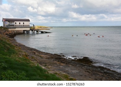 Kayaker's pass the lifeboat station at Moelfre on Anglesey in North Wales, UK. Taken  26 October 2018