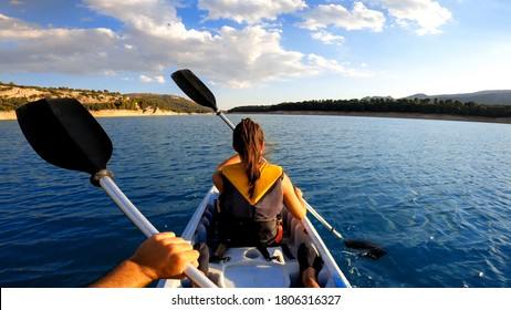 Kayakers rowing at lake. Pov of woman kayaking in beautiful landscape at Embalse de la Bolera, Spain. Aquatic sports in kayak during summer concept.
