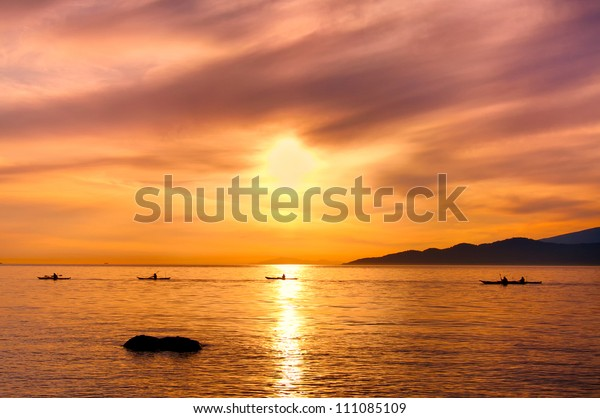 Kayakers silhouette on ocean during orange sunset was taken off the shores of Vancouver, British Columbia, Canada
