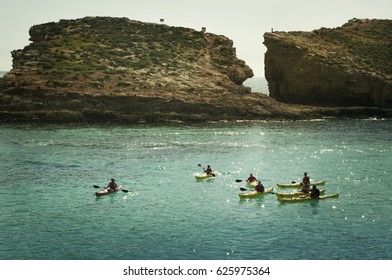 kayakers swimming through the crystal waters of Blue Lagoon. Comino Island. Sunny day, natural light and reflections on a turquoise water. Active summer.