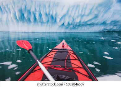 kayaking in Antarctica, red canoe boat with paddle  near blue iceberg