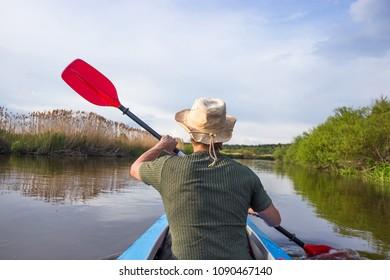 Kayaking on beautiful nature at summer sunny day. Sport people having fun.