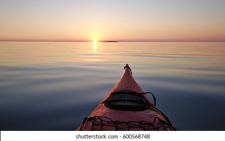 Kayaking on peaceful calm water towards setting sun. Shot from point of view of the paddler.