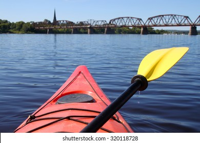 Kayaking on the Saint John River  in Fredericton, New Brunswick in Atlantic Canada with walking bridge and church in the distance. Shallow depth of field