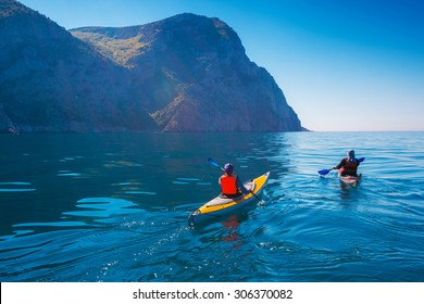 Kayaking. People swim in the sea kayak near the mountains. Adventures on the water.