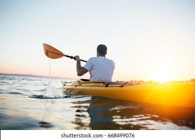 Kayaking at sunset sea. Man paddling the kayak