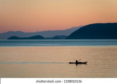 Kayaking at Sunset Through the San Juan Islands of Washington State. A kayaker paddles past Orcas Island in the Salish Sea during a beautiful sunset.