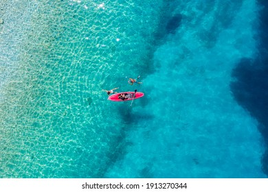 Kayaking. Sup. Aerial view of floating board and people on blue sea at sunny day. Travel and active life image. Mediterranean sea.